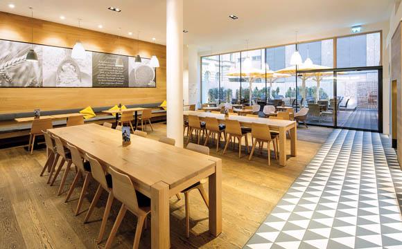 Sauber: getrennt Die klassischen Schachbrettfliesen in ungewöhnlichem Dekor trennen den Gastraum vom Verkaufsraum, ohne dem hellen Eichenholz den Auftritt zu nehmen.