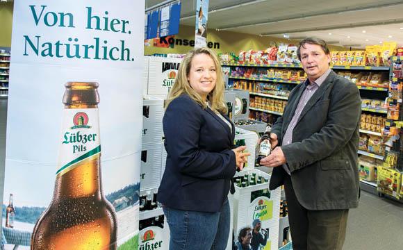 Lübzer Brand Managerin Claudia Schubert und Werner Pechstein, Carlsberg Gebietsverkaufsleiter, präsentieren den neuen Auftritt der Marke am PoS