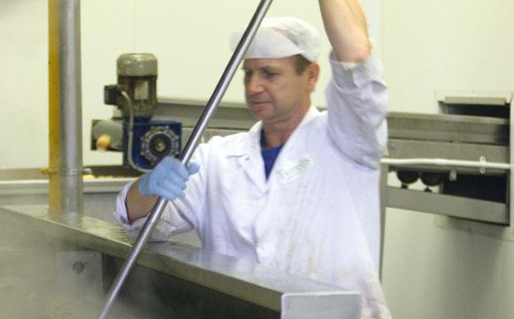 In großen Frittierkesseln werden die Chips chargenweise gegart und dabei von Hand bewegt.
