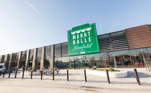 """An einen Marktplatz in Italien soll das neue Konzept erinnern und eher wenig an einen Real- Markt. Deshalb ist """"Real"""" auf dem grün-weißen Logo nur klein zu lesen."""