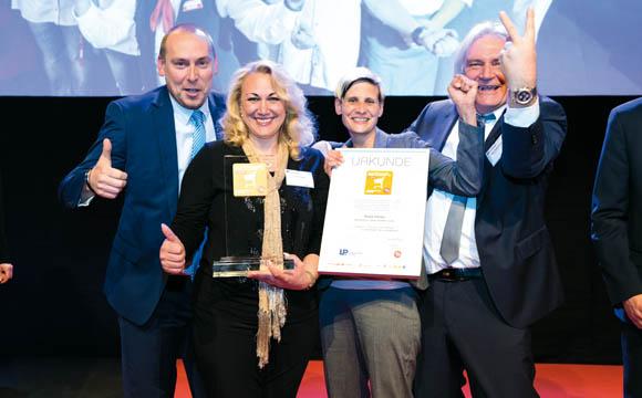 Gewinner - Filialisten über 2.000 qm<br /> Rewe-Center, Georgscheller Str. 6-9, 61231 Bad Nauheim<br /> Schon zum zweiten Markt steht Marktleiterin Elena Schmidt (mit Pokal) als strahlende Preisträgerin auf der Bühne. Das Team hat den Titel aus dem Jahr 2015 erfolgreich zurückerobert.
