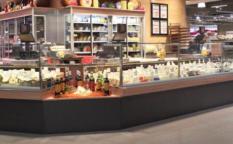 Transparent: An der Mittelinsel mit den Bedientheken und den gekühlten Rückschränken erhalten die Kunden Einblick in die Warenlagerung.