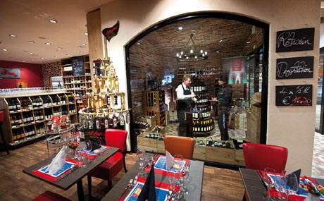 Speziell die Weinabteilung stellt hohe Anforderungen an die Fachkompetenz des Marktes. Zurheide Feine Kost in Düsseldorf hat dafür einen transparenten Rückzugsraum mit Weinkeller-Atmosphäre geschaffen. (Bildquelle: Kämper)