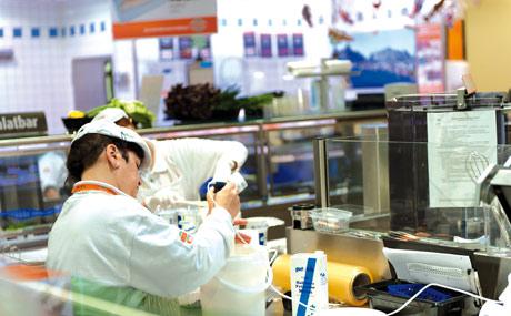 Immer unter Beobachtung: Die Arbeitsplätze sind von vier Seiten aus einsehbar. Die Mitarbeiter schnippeln und rühren, füllen auf, räumen ab – und halten die Theken sauber.