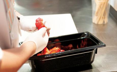 Genau wie zuhause: Ein Globus-Mitarbeiter schneidet den Stielansatz weg und halbiert die Erdbeeren.